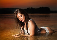 Sexy brunette woman in lingerie laying in river water. Young female relaxing on the beach during sunset. Perfect body girl Royalty Free Stock Images
