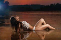 Sexy brunette woman in lingerie laying in river water. Young female relaxing on the beach during sunset. Perfect body girl Stock Images