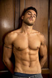 Sexy handsome young man standing shirtless against Royalty Free Stock Photos