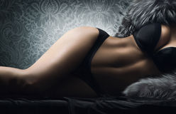 A sexy woman laying in erotic lingerie and fur Stock Photos