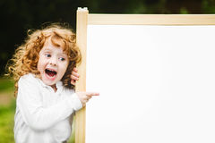 Shocked and happy child with school blackboard. Royalty Free Stock Images