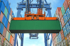 Shore crane loading containers in freight ship Stock Images