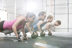 Side view of determined people doing pushups with kettlebells at crossfit gym Royalty Free Stock Photography