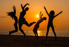 Silhouettes a young people having fun on a beach Royalty Free Stock Photo
