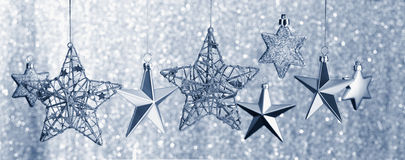 Silver Stars Hanging against Glitter Background Royalty Free Stock Photography
