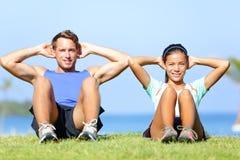 Sit ups - fitness couple exercising sit up outside Stock Image