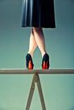 Slender female legs crossed on the table Stock Photo