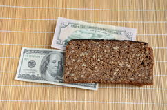 Slice of brown bread with US dollar bills Royalty Free Stock Photography