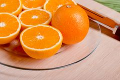 Sliced ripe appetizing orange on a cutting board on a green tabl Royalty Free Stock Image