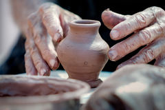 Small clay vase and hands of working potter Stock Images