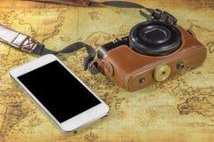 Smartphone och fick- kamera på en världskarta Arkivfoton