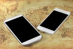 Smartphoneon en världskarta Royaltyfri Fotografi