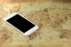 Smartphoneon en världskarta Royaltyfria Foton