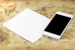 Smartphoneon en världskarta Arkivfoto