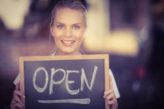 Smiling blonde waitress showing chalkboard with open sign Royalty Free Stock Photo