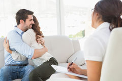 Smiling couple hugging in front of their therapist Stock Image
