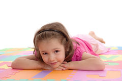 Smiling girl child resting on kids alphabet floor Royalty Free Stock Photos