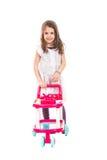Smiling girl pushing pram toy Stock Photography
