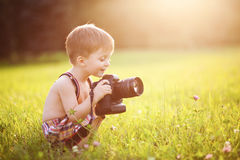 Smiling kid holding a DSLR camera in park Stock Photography