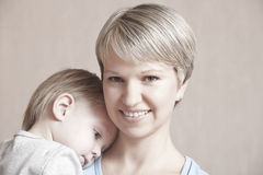Smiling Mother With Baby Boy Leaning On Her Shoulders Stock Photo