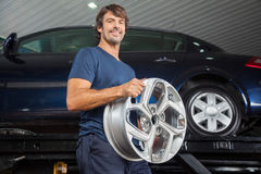Smiling Technician Holding Alloy At Repair Shop Royalty Free Stock Photo