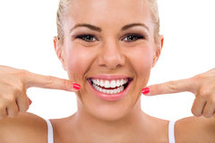 Smiling woman pointing in her perfect teeth Stock Photography