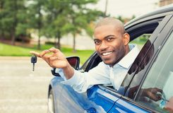 Smiling, young man sitting in his new car showing keys Stock Photos