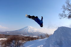 Snowboarder sending it off backcountry jump Royalty Free Stock Images