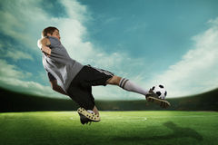 Soccer player kicking the soccer ball in mid air, in the stadium with the sky Royalty Free Stock Photo