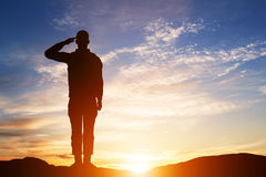 Soldier salute. Silhouette on sunset sky. Army, military. Stock Photography