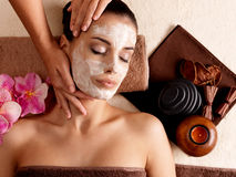 Spa massage for woman with facial mask on face Royalty Free Stock Photography