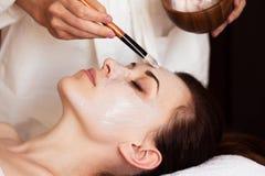 Spa treatment. Beautiful woman with facial mask at beauty salon. Royalty Free Stock Photos