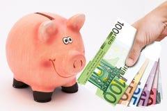 Sparschwein- und Geldturm Lizenzfreie Stockfotos