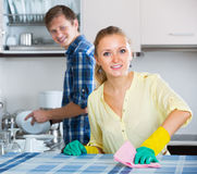 Spouses doing regular housework and polishing Royalty Free Stock Photos