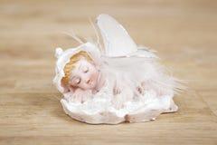 Statua miniatura dell'angelo bianco con le ali su superficie di legno Fotografia Stock Libera da Diritti