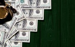 Sterta pieniędzy dolary kłaść out jak drabina z antykwarskim złocistym zegarkiem na ciemnozielonym stylizowanym drewnianym tle Obraz Stock