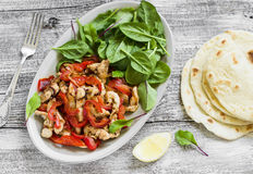 Stir fry of chicken breast and sweet red peppers, fresh spinach and homemade tortillas Royalty Free Stock Photo