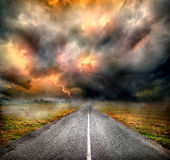 Storm clouds and lightning over highway Stock Photo