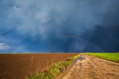 Storm sky and rainbow Stock Photos