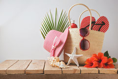 Summer beach bag and hibiscus flowers on wooden table. Summer holiday vacation concept. View from above Royalty Free Stock Photography
