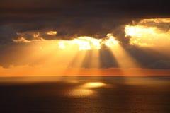 Sunbeams through dark clouds over ocean Stock Images