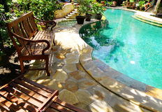 Sunny outdoor swimming pool and patio furniture Royalty Free Stock Photography
