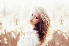 Sunny portrait of a beautiful young blonde girl in a field in white pullover, the concept of health and beauty Stock Photography