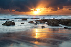 Sunrise landscape of ocean with waves clouds and rocks Stock Image