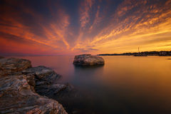 Sunset by the ocean with rock in the middle of the water Royalty Free Stock Images