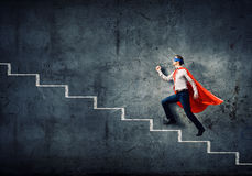 Superman on ladder Royalty Free Stock Photo