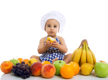 Sweet beautiful baby cook eating healthy fruits Stock Image
