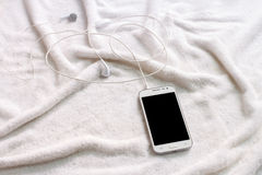 Téléphone portable blanc avec des écouteurs sur une serviette Photographie stock