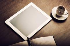 Tablet PC und ein Kaffee und ein Notizbuch mit Stift auf dem Büroschreibtisch Lizenzfreies Stockfoto