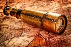 Tappningkikaren ligger på en forntida världskarta Arkivbild